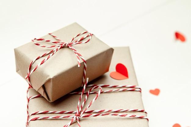 Caja de regalo del día de san valentín y corazones de papel rojo sobre fondo blanco.