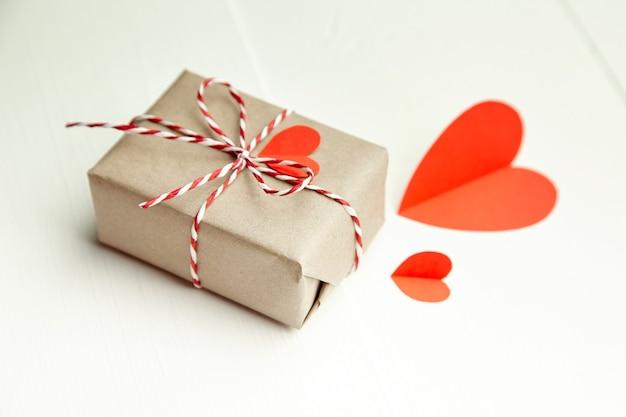 Caja de regalo del día de san valentín con corazones de papel rojo sobre fondo blanco.