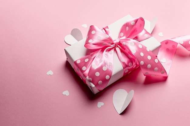Caja de regalo del día de san valentín con corazones de papel sobre fondo rosa