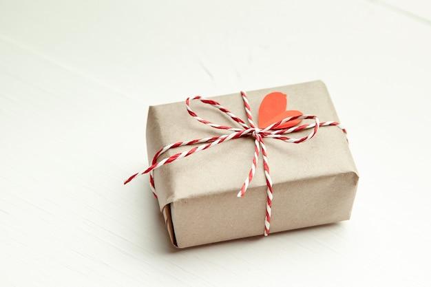 Caja de regalo del día de san valentín decorada con corazón rojo sobre fondo blanco.