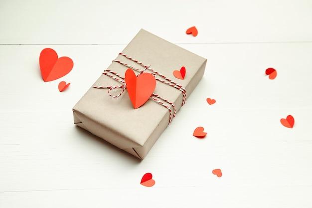 Caja de regalo del día de san valentín decorada con corazones de papel rojo sobre fondo blanco de madera