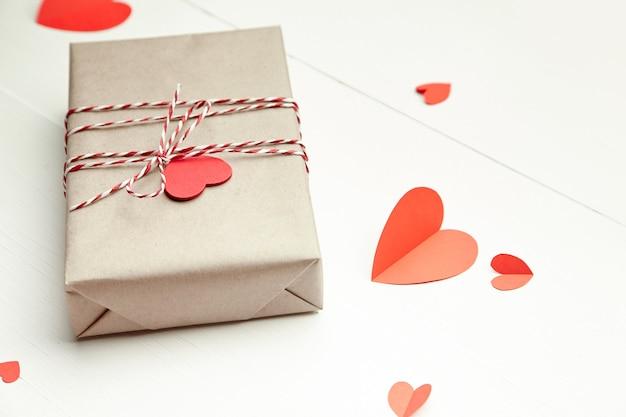 Caja de regalo del día de san valentín decorada con corazones rojos sobre fondo blanco de madera