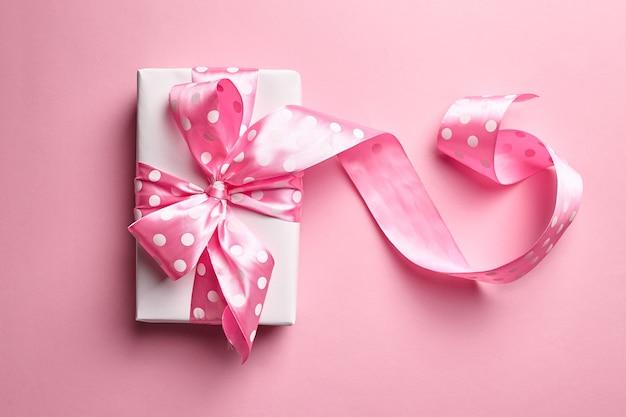 Caja de regalo del día de san valentín con lazo grande sobre fondo rosa