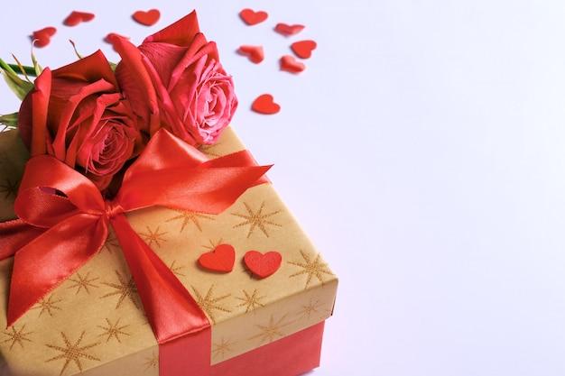 Caja de regalo dorada con cinta roja, rosas y pequeños corazones para el día de san valentín