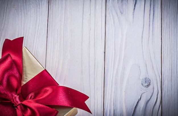 Caja de regalo dorada en concepto de vacaciones de espacio de copia de tablero de madera