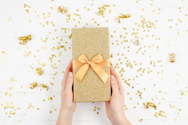 Caja de regalo dorada con confeti