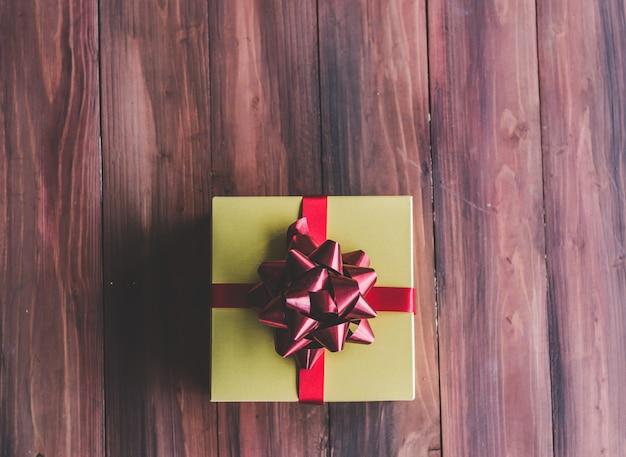 Caja de regalo dorada y lazo rojo en madera.