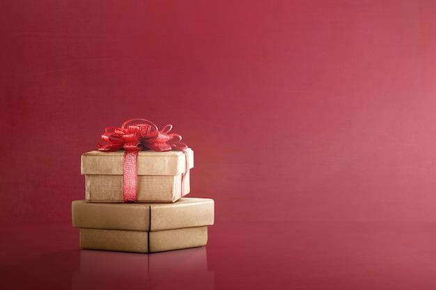 Caja de regalo dorada con lazo rojo.