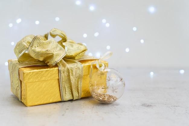 Caja de regalo dorada de navidad con lazo y bola navideña