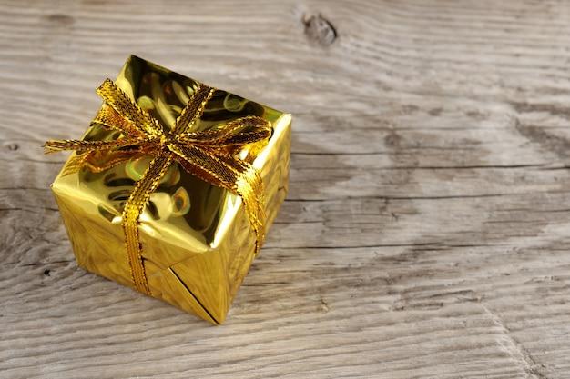 Caja de regalo dorada sobre fondo de madera