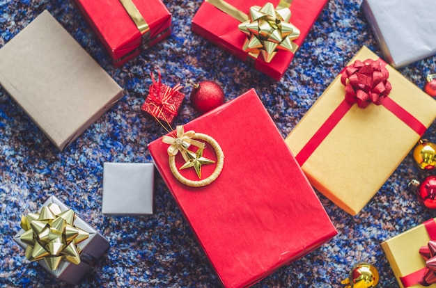 Caja de regalo dorado y cinta roja sobre fondo de color