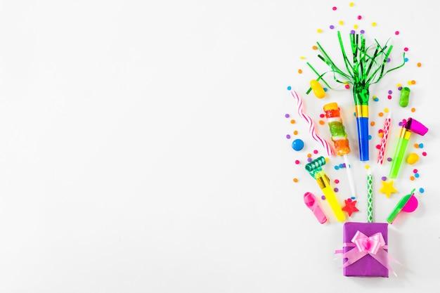 Caja de regalo; dulces y accesorios de fiesta sobre fondo blanco