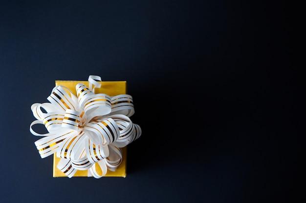 La caja de regalo elegante envuelta en blanco y oro rayó la cinta en fondo texturizado negro.