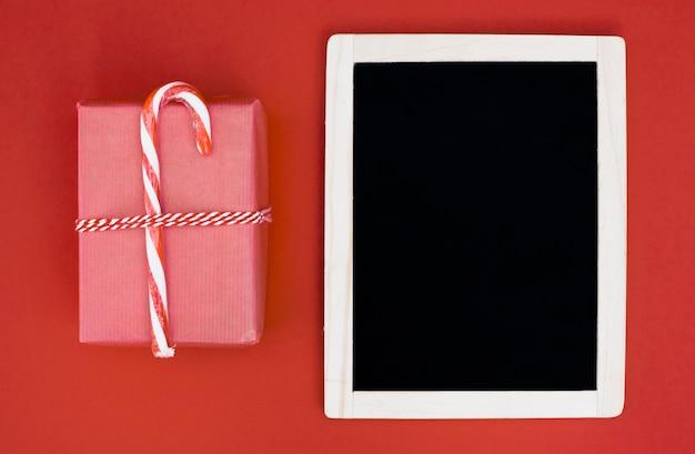 Caja de regalo en envoltura con bastón de caramelo cerca del marco de fotos