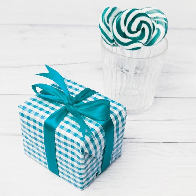 Caja de regalo en envoltura cerca de vidrio con piruletas