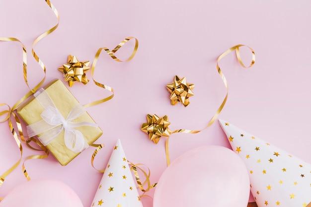 Caja de regalo envuelta; arco; flámula; globo y sombrero de fiesta sobre fondo rosa