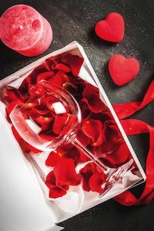 Caja de regalo envuelta en blanco con cinta roja, con pétalos de rosas en copa de vino