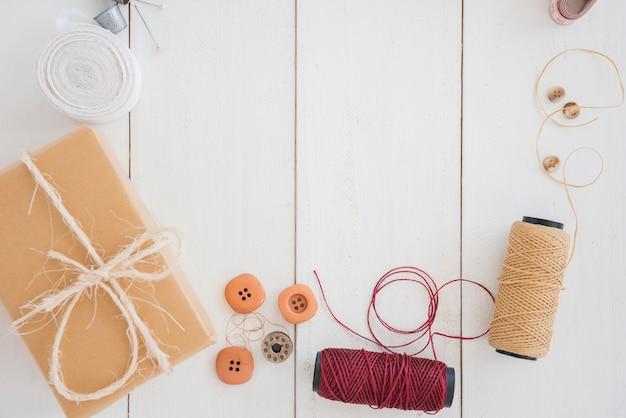 Caja de regalo envuelta; botones; carrete y dedal en escritorio de madera blanca