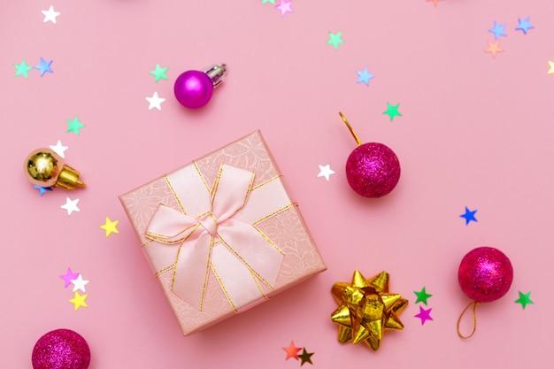 Caja de regalo envuelta con cinta, bolas decorativas y copo de nieve sobre fondo de papel rosa de colores con caramelos en forma de estrellas. regalo de navidad. concepto de vacaciones. imagen con espacio de copia. vista plana endecha desde arriba