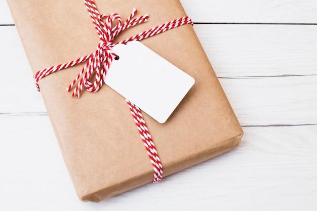 Caja de regalo envuelta con hilo y etiqueta.