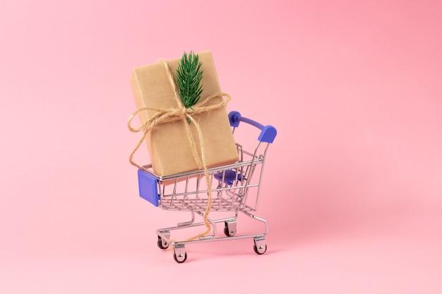 Caja de regalo envuelta en papel kraft en una cesta de la compra.