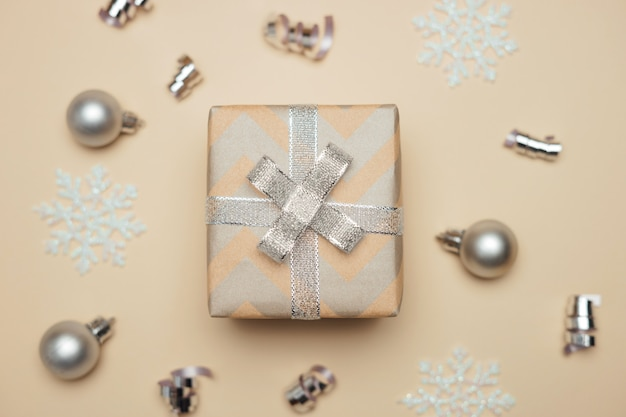 Caja regalo envuelta en papel kraft con cinta plateada en navidad.