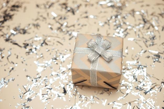 Caja de regalo envuelta en papel kraft con cinta plateada sobre beige brillante.