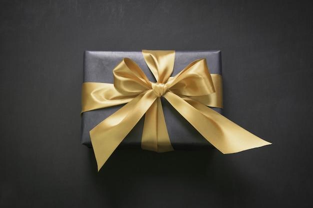 Caja de regalo envuelta en papel negro con cinta dorada sobre superficie negra.