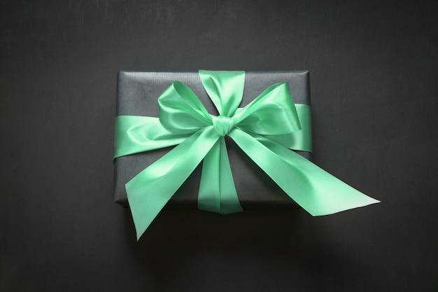 Caja de regalo envuelta en papel negro con cinta neo mint sobre superficie negra.
