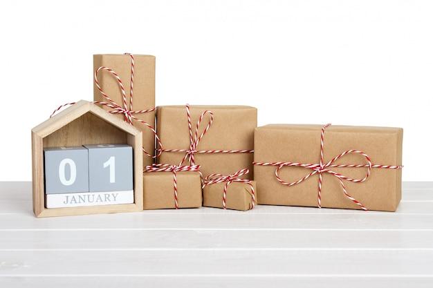 Caja de regalo envuelta en papel reciclado con lazo de cinta y calendario.