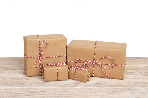 Caja de regalo envuelta en papel reciclado con lazo de cinta en la mesa de madera.