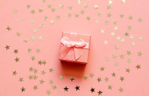 Caja de regalo con estrellas holográficas doradas.