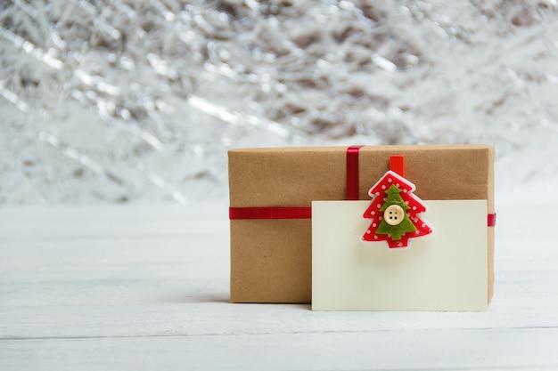 Caja de regalo con etiqueta de regalo en blanco sobre fondo blanco de madera