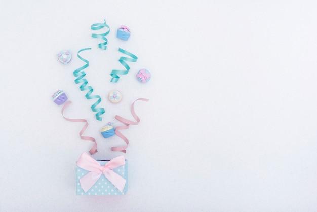 Caja de regalo festivo con cintas y cupcakes.