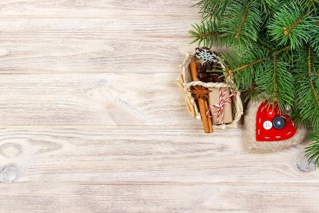 Caja de regalo festivo con corazón, anice estrellado, canasta, canela y copo de nieve sobre fondo de madera. regalos de navidad con copyspace