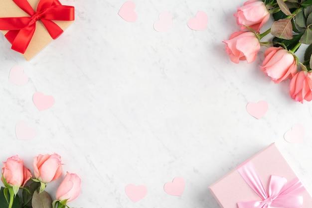 Caja de regalo y flor rosa rosa sobre la superficie de la mesa de mármol blanco para el concepto de diseño de saludo de vacaciones del día de la madre.