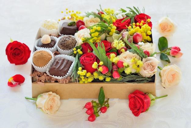 Caja de regalo con flores y dulces.