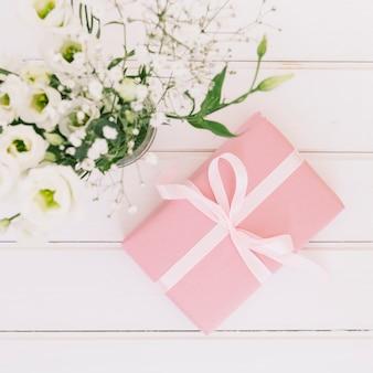 Caja de regalo con flores en florero.