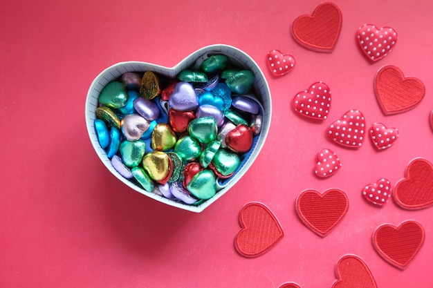 Caja de regalo en forma de corazón con caramelo en espacio rojo