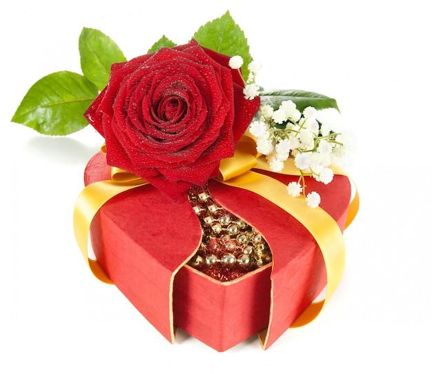 Caja de regalo en forma de corazón decorada con rosa roja, aislada en blanco