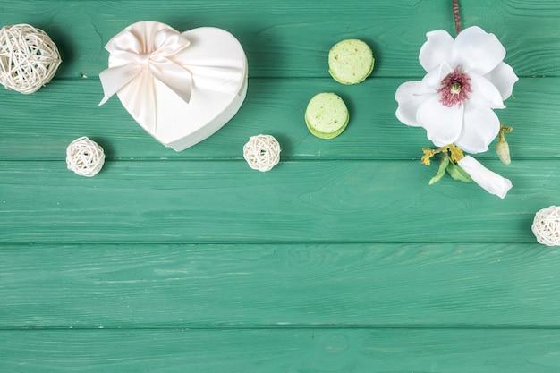 Caja de regalo en forma de corazón con flores y macarrones.