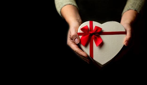 Caja de regalo en forma de corazón en manos sobre fondo negro