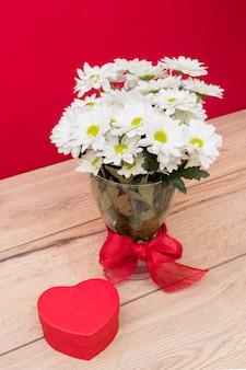 Caja de regalo en forma de corazón con ramo de flores en florero.