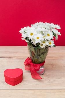 Caja de regalo en forma de corazón con ramo de margaritas en florero