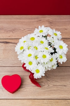 Caja de regalo en forma de corazón con ramo de margaritas.