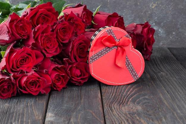Caja de regalo en forma de corazón y ramo de rosas rojas