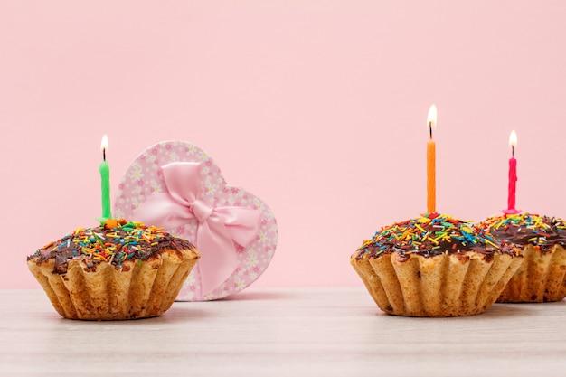 Caja de regalo en forma de corazón y sabrosos muffins de cumpleaños, decorada con velas festivas ardientes sobre fondo de madera y rosa con espacio de copia .. concepto de feliz cumpleaños.