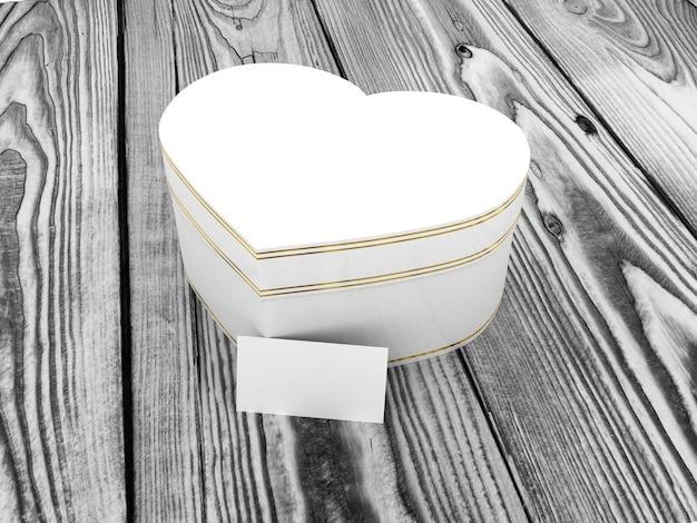 Caja de regalo en forma de corazón sobre mesa de madera