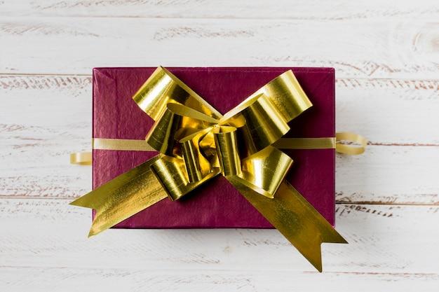 Caja de regalo granate con cinta dorada sobre mesa de madera.