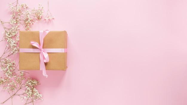 Caja de regalo grande con ramas de flores en la mesa